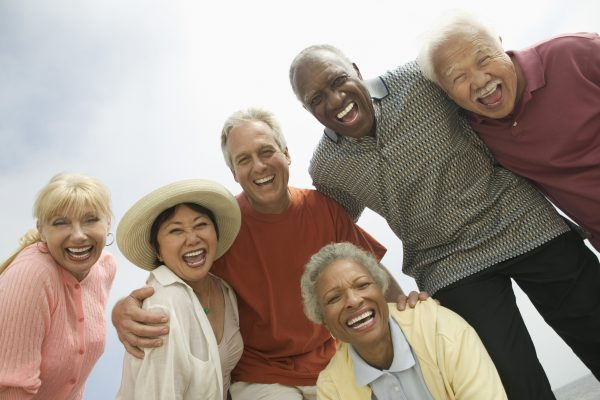 Group of older friends laughing while huddled for a photo