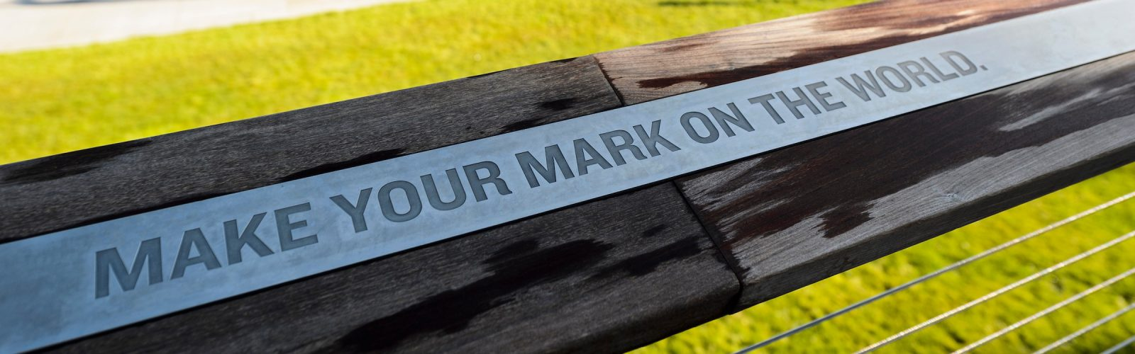 Alumni Park Plaque saying make your mark on the world