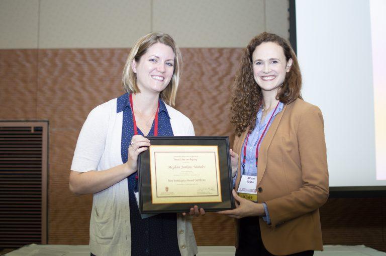 Meghan Jenkins Morales holding her New Investigator Award with IOA Administrator, Allison Zenke