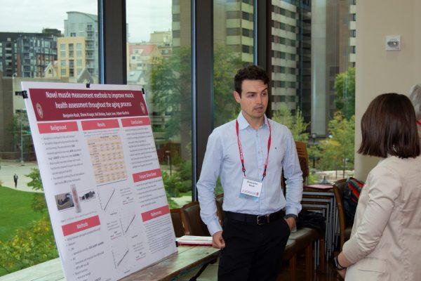Poster Presenter describing his poster to an attendee