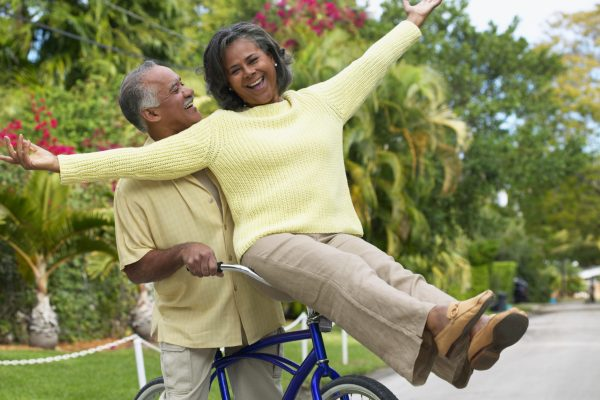 woman with arms outstretched riding on handlebar of mans bike laughing