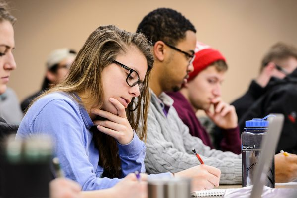 Undergraduate students take notes in a classroom