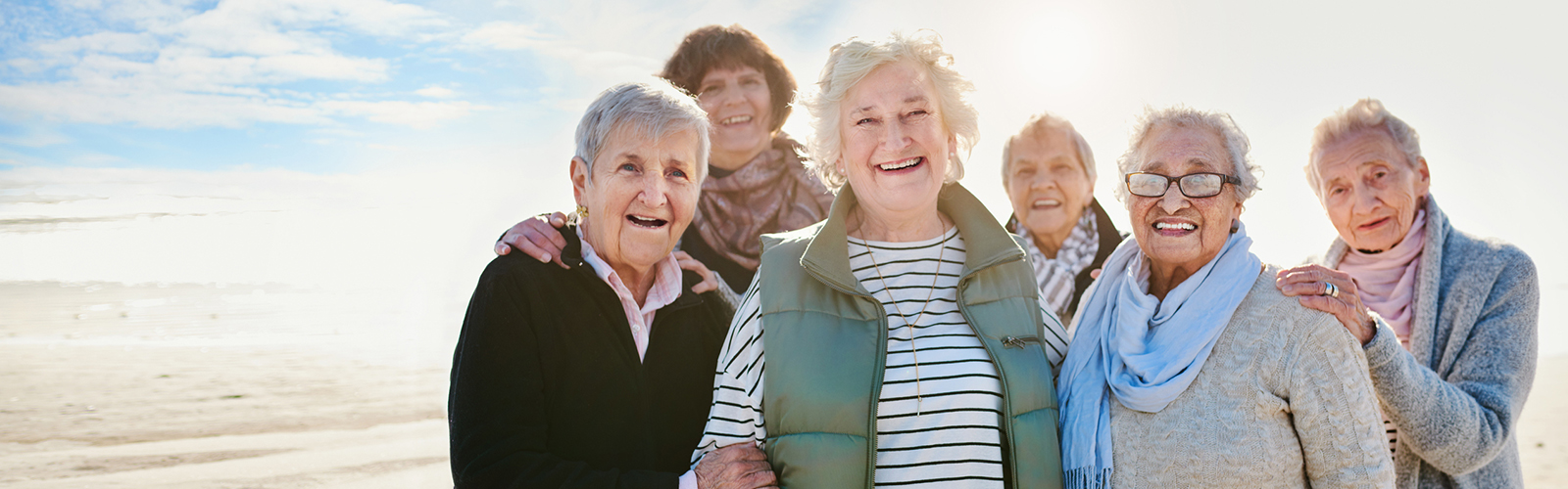 Group of six smiling older women on a beach with a bright sky