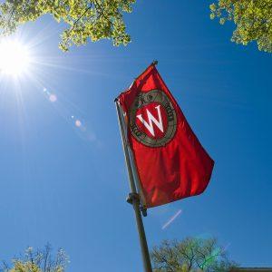 Red UW Crest banner against blue sky