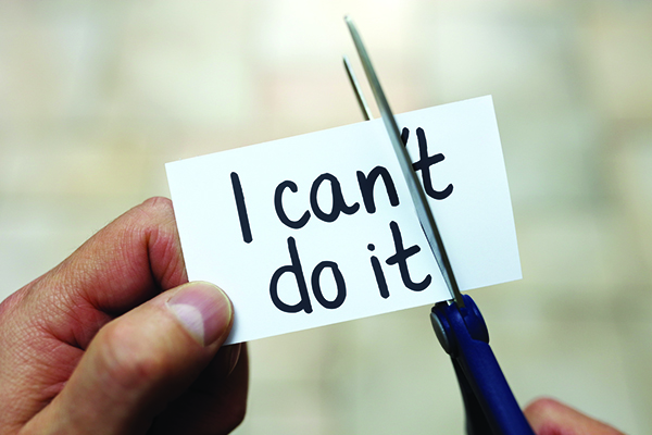 """Hands using scissors to remove the word """"can't"""" to read """"I can do it"""" on a slip of paper"""