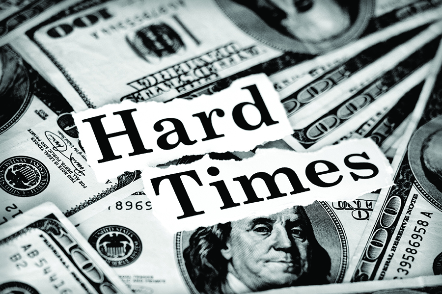 "Black and white photo of the words ""Hard Times"" typed over a pile of 100 dollar bills"