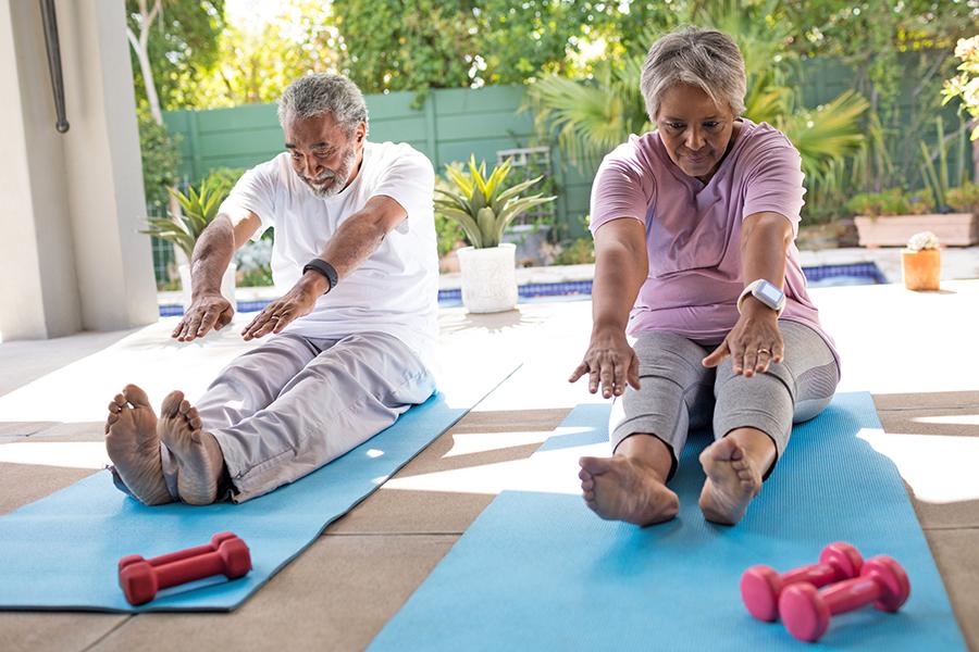 Senior couple doing stretching exercise on blue yoga mats
