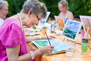Older woman smiling while painting with a group.