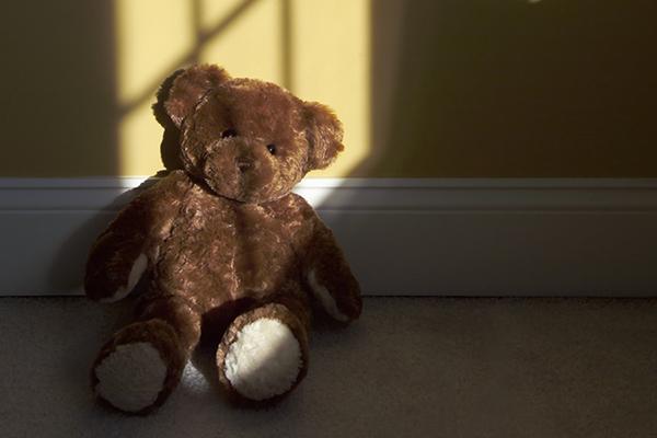 A teddy bear lies alone in a room.