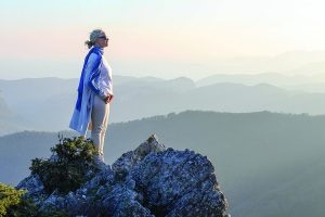 Woman looks out over distant mountains