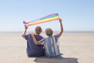 Mature female couple waving a Pride flag