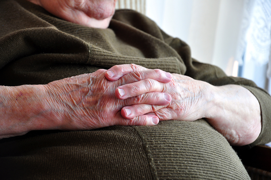 Hands of a senior person crossed on their stomach