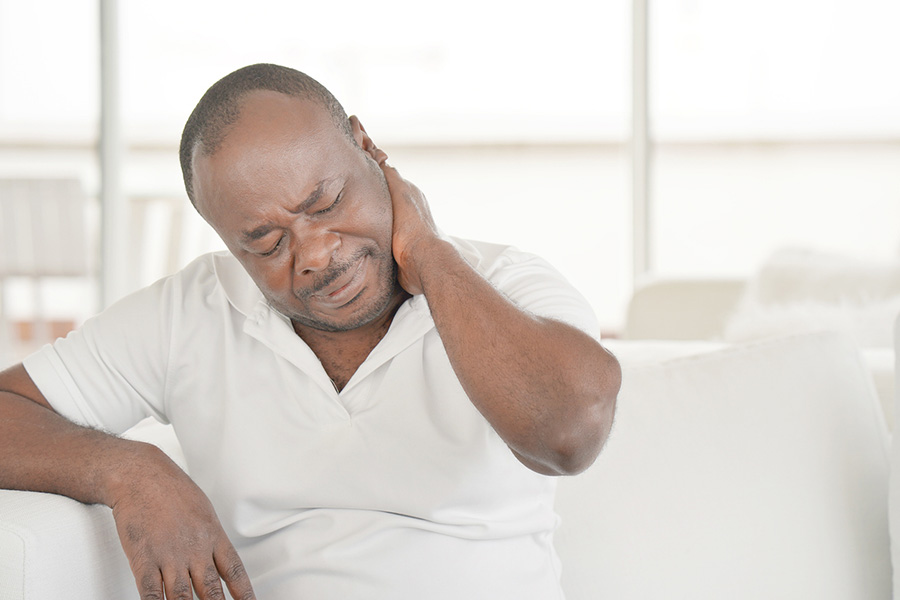 African American man suffering from neck pain at home on couch