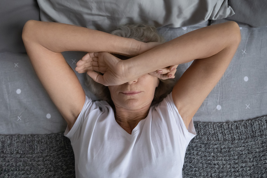 Aged woman lying on bed suffers from insomnia